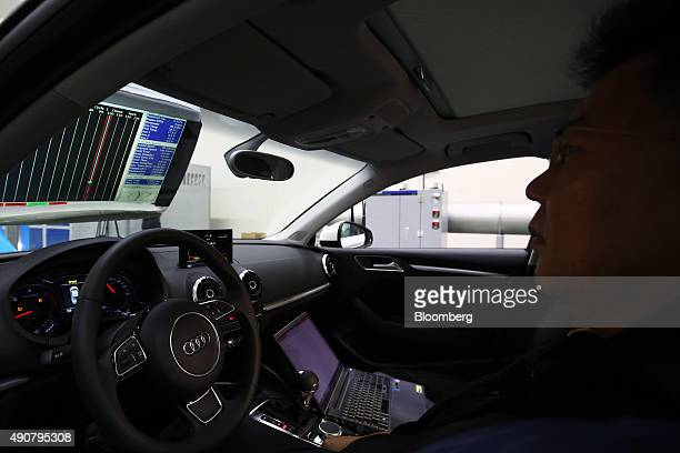 An employee looks at a screen as an Audi AG A3 35 TDI emissions certification vehicle produced by Volkswagen AG is tested inside the Transportation...