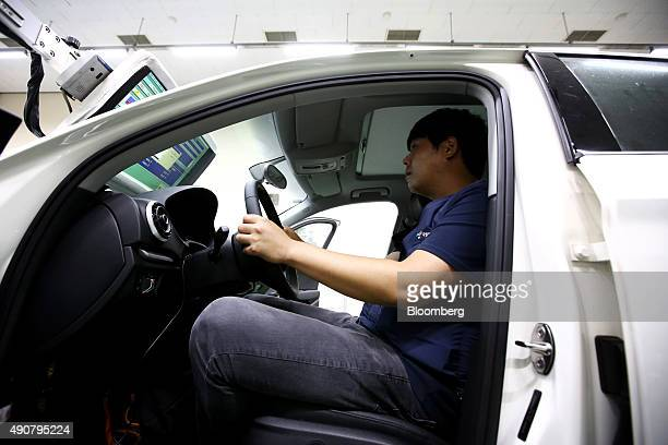 An employee looks at a screen showing laboratory conditions as he sits inside an Audi AG A3 35 TDI emissions certification vehicle produced by...