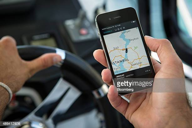 An employee looks at a smartphone Uber app with his location as he pilots a Beneteau SA motor boat owned by NavetteTezman Holding and operated...