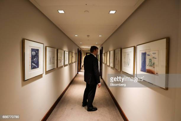 An employee looks at artwork by the artist David Hockney hanging on the wall of the De Beers SA headquarters on Charterhouse Street in London UK on...