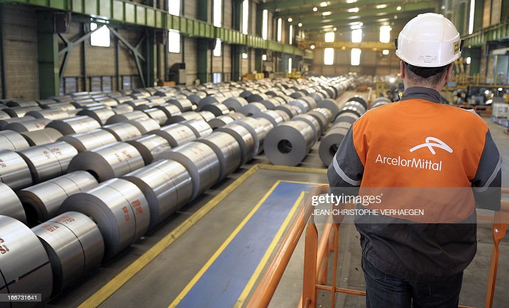 An employee looks at coils of steel treated by galvanization are stored in the world's largest steel maker ArcelorMittal's 'cold factory' of the northeastern France plant of Florange, on April 16, 2013. Usibor steel (weight savings and improved crashworthiness) are producted in the cold factory. AFP PHOTO / JEAN-CHRISTOPHE VERHAEGEN