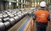 An employee looks at coils of steel treated by galvanization are stored in the world's largest steel maker ArcelorMittal's 'cold factory' of the...