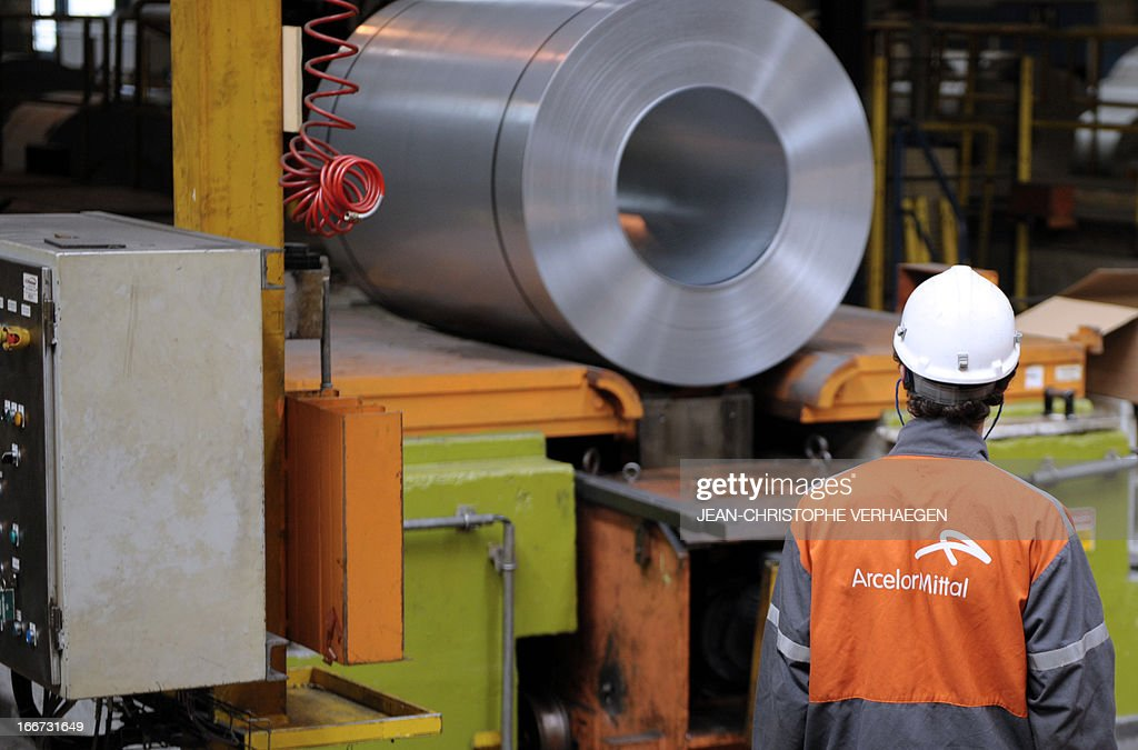 An employee looks at coils of steel treated by galvanization are stored in the world's largest steel maker ArcelorMittal's 'cold factory' of the northeastern France plant of Florange, on April 16, 2013. Usibor steel (weight savings and improved crashworthiness) are producted in the cold factory.