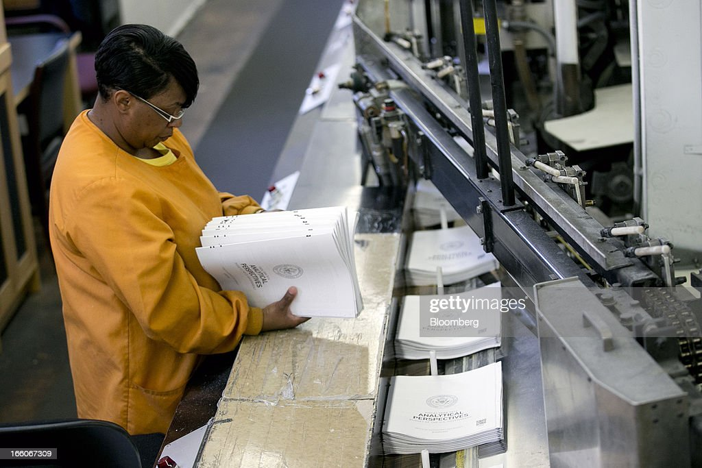 An employee looks at copies of the Fiscal Year 2014 Budget at the U.S. Government Printing Office in Washington, D.C., U.S., on Monday, April 8, 2013. Less than a week after job-creation figures fell short of expectations and underscored the U.S. economy's fragility, President Barack Obama will send Congress a budget that doesn't include the stimulus his allies say is needed and instead embraces cuts in an appeal to Republicans. Photographer: Andrew Harrer/Bloomberg via Getty Images