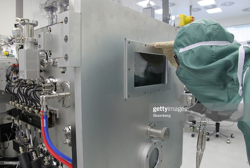 An employee looks into a processing box during organic light-emitting diode (OLED) production in a clean room at the Merck KGaA research center in Darmstadt, near Frankfurt, Germany, on Tuesday, Sept. 23, 2010. Merck KGaA is developing liquid crystals for 3-D televisions that don't require special glasses as the company seeks to bolster sales of the fastest-growing use for the product. Photographer: Hannelore Foerster/Bloomberg via Getty Images