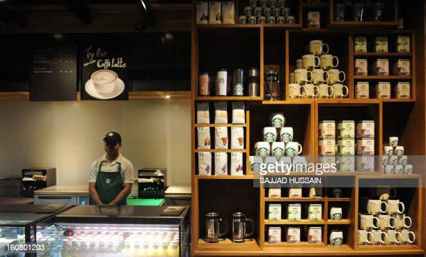 An employee looks on behind the counter at the newlyinaugurated Starbucks outlet in New Delhi on February 6 2013 Starbucks the world's biggest coffee...