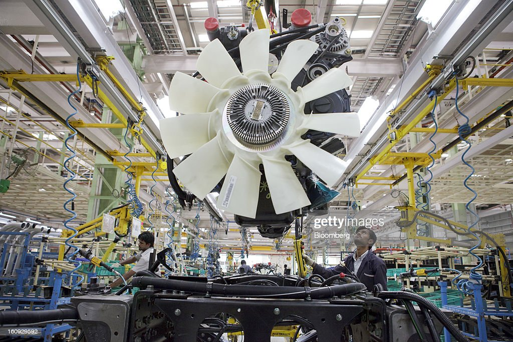 An employee lowers an engine onto a chassis on the assembly line for the Mahindra & Mahindra Ltd. Navistar truck at the company's factory in Chakan, Maharashtra, India, on Wednesday, Feb. 6, 2013. Mahindra & Mahindra is scheduled to announce third-quarter earnings today. Photographer: Kuni Takahashi/Bloomberg via Getty Images