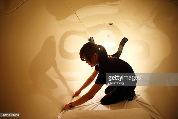 An employee makes a bed inside a capsule unit in the Nine Hours Narita Airport capsule hotel operated by nine hours Inc at Narita Airport in Narita...