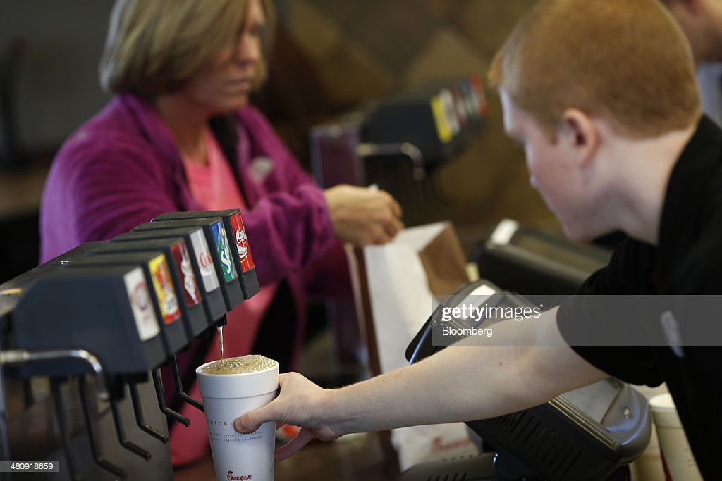An employee makes a drink for a customer at a Chick-fil-A Inc. restaurant in Bowling Green, Kentucky, U.S., on Tuesday, Mar. 25, 2014. The U.S. economy grew more rapidly in the fourth quarter than previously estimated as consumer spending climbed by the most in three years, showing the expansion had momentum heading into this years harsh winter. Photographer: Luke Sharrett/Bloomberg via Getty Images