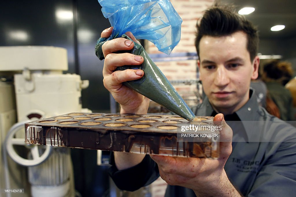 An employee makes chocolates in French chef Alain Ducasse's new establishment, the 'Manufacture de chocolat' (Chocolate Factory), on February 19, 2013 in Paris.
