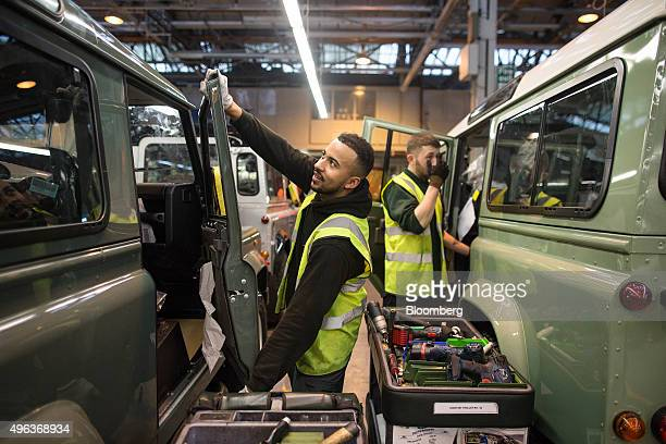 An employee makes final adjustments to a Land Rover Defender automobile at Tata Motors Ltd's Jaguar Land Rover vehicle manufacturing plant in...