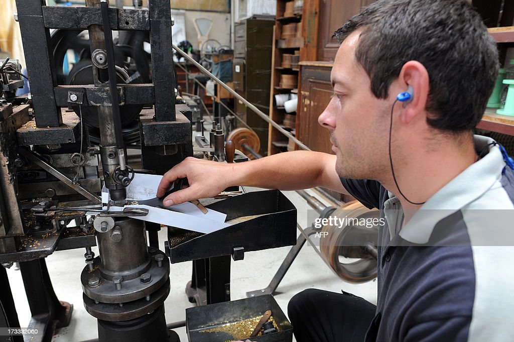 An employee makes glitters from gold wires with a trip hammer, on July 9, 2013, at the B-BA plant, a subsidiary of Marck Group, in La Chartre-sur-le-Loir, western France. B-BA, one of the last in France to maintain, since 1848, the art of traditional military trimmings, manufactures the braids, badges and epaulettes worn during Bastille Day.