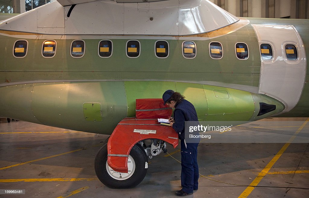 An employee makes notes as she checks the fuselage of an ATR-72 turboprop aircraft, manufactured by Avions de Transport Regional (ATR), during assembly at the company's production facility in Colomiers, France, on Wednesday, Jan. 23, 2013. ATR, the world's largest maker of turbo-propeller airliners, reported record profit for 2012, even as it fell short of its shipment target amid production delays. Photographer: Balint Porneczi/Bloomberg via Getty Images