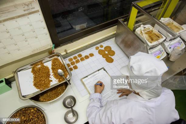 An employee makes notes as she examines garlic samples in a quality control area of the Nithi Foods Co factory in the San Pa Tong district of Chiang...
