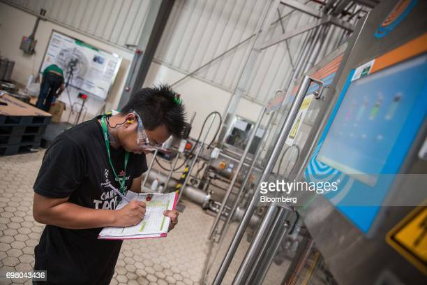 An employee makes notes while checking equipment in the bottling plant at the Heineken NV brewery in Yangon Myanmar on June 15 2017 Heineken is...