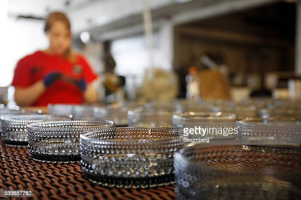 An employee makes quality control checks on Kastehelmi style glass bowls at the Iittala Oyj glass factory operated by Fiskars Oyj in Hameenlinna...