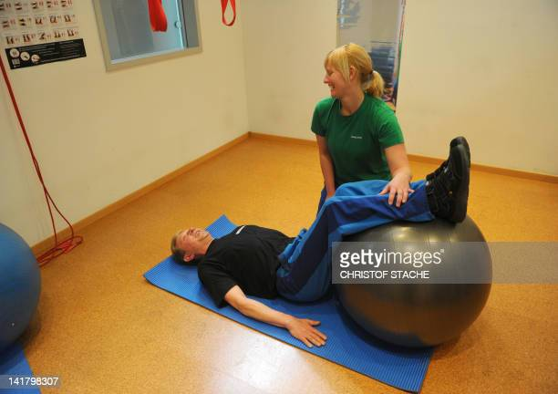 An employee makes stretching exercises with physiotherapist Daniela Arndt at the relaxation room of the German carmaker BMW plant in Dingolfing...