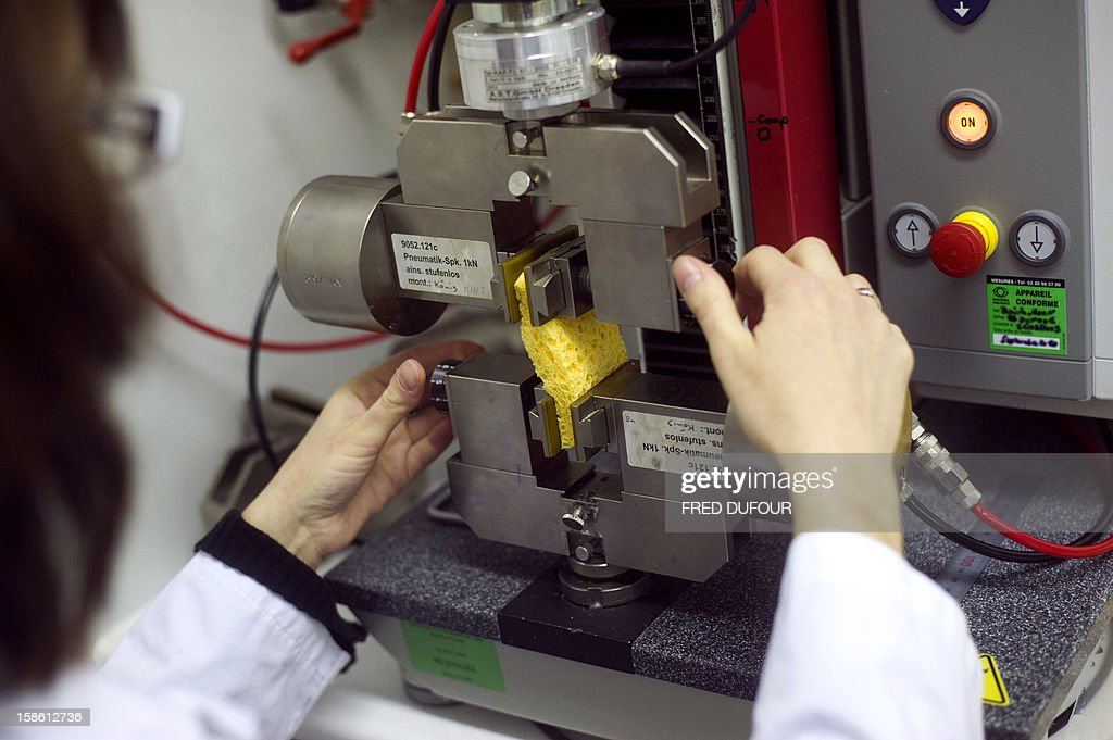 An employee makes tests on a sponge in the research laboratory at the factory of French sponge brand Spontex on December 19, 2012 in Beauvais.