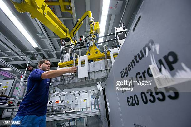 An employee maneuvers fully assembled lithiumion batteries before packaging at the Bayerische Motoren Werke AG automobile manufacturing plant in...