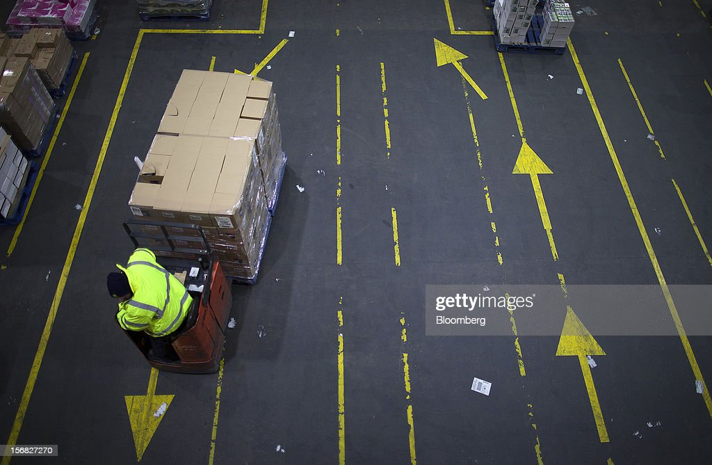 An employee maneuvers goods with a pallet truck inside WM Morrison Supermarkets Plc's distribution center in Wakefield, U.K., on Thursday, Nov. 22, 2012. Britain's economy will return to growth next year after stagnating in 2012, with expansion weighted in the second half, according to Bank of England projections published yesterday. Photographer: Simon Dawson/Bloomberg via Getty Images