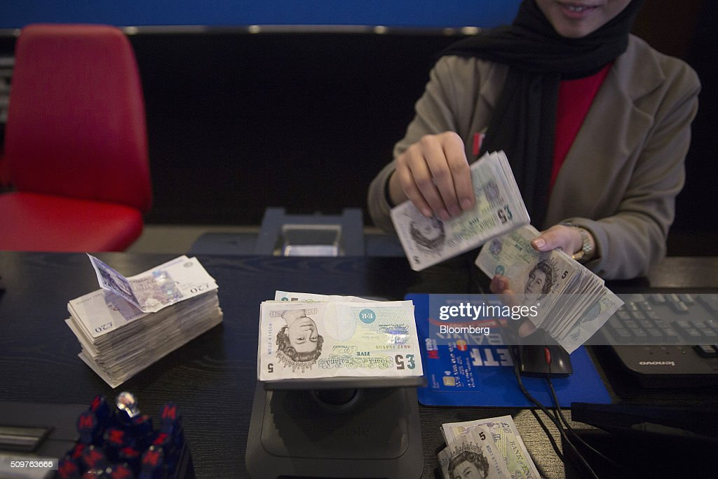 An employee manually counts five pound currency bank notes inside a branch of Metro Bank Plc in London, U.K., on Friday, Feb. 12, 2016. Metro Bank, the British lender backed by wealthy American financiers including Steven Cohen, plans to sell shares to existing investors before going public on the London Stock Exchange. Photographer: Simon Dawson/Bloomberg via Getty Images