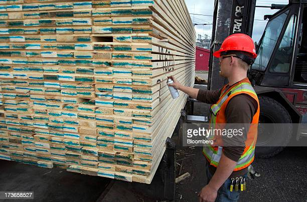 An employee marks a load of lumber at the West Fraser Timber Co sawmill in Quesnel British Columbia Canada on Thursday July 11 2013 West Fraser...
