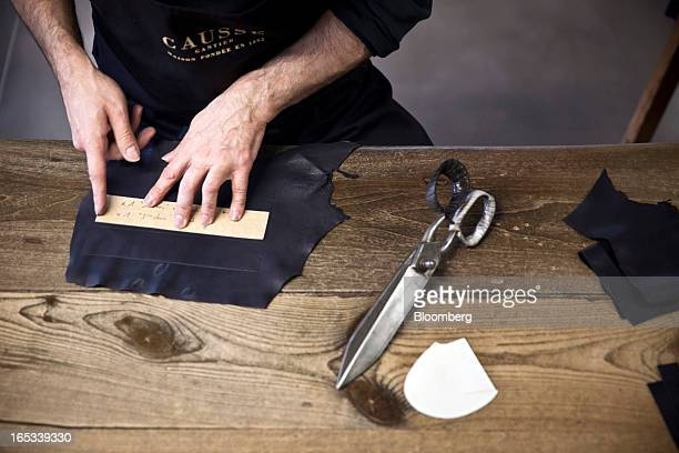 An employee measures a section of leather hide during the manufacture of handmade luxury gloves by Causse Gantier in Millau France on Tuesday April 2...