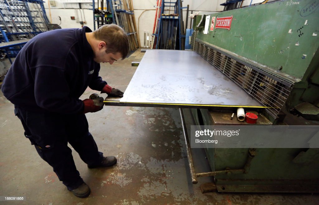 An employee measures a sheet of steel before cutting to size for a customer in the warehouse at Metal Supermarkets in Southampton, U.K., on Friday, Nov. 15, 2013. The Bank of England sees gross domestic product rising 0.9 percent this quarter before easing in the early part of 2014, according to its new projections. Photographer: Chris Ratcliffe/Bloomberg via Getty Images