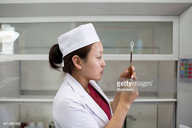 An employee measures a solution used to analyze milk inside a quality control laboratory at the APU JSC dairy plant in Ulaanbaatar Mongolia on...