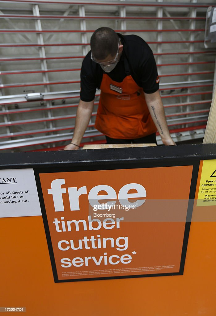 An employee measures timber prior to cutting inside a B&Q home improvement store, operated by Kingfisher Plc, in London, U.K., on Tuesday, July 16, 2013. Financial assistance for first-time home buyers in Britain is likely to prompt a resurgence of do-it-yourself spending after several years of decline, according to Kingfisher Plc Chief Executive Officer Ian Cheshire. Photographer: Chris Ratcliffe/Bloomberg via Getty Images