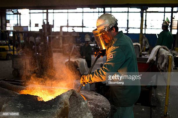 An employee mixes chemicals in a batch of molten iron in a melting pot before it is poured into molds in the foundry area of Trumbull Metal...