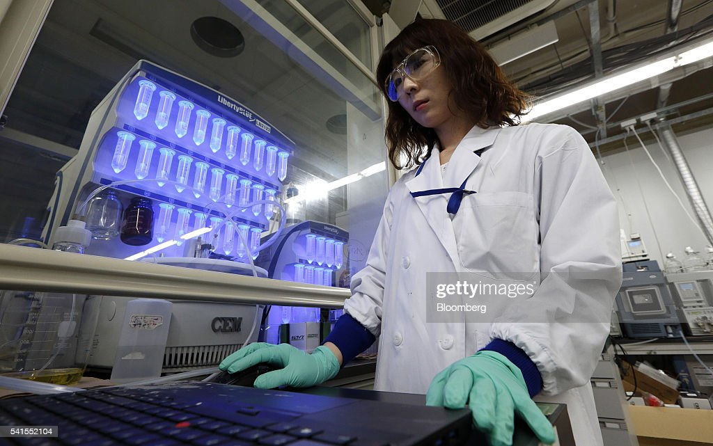 An employee monitors a laptop computer as centrifuge tubes containing amino acid are seen in an automated microwave peptide synthesizer at the...