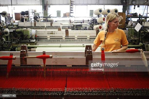 An employee monitors a machine as it weaves red wool thread into blankets at the Woolrich Inc woolen mill in Woolrich Pennsylvania US on Wednesday...