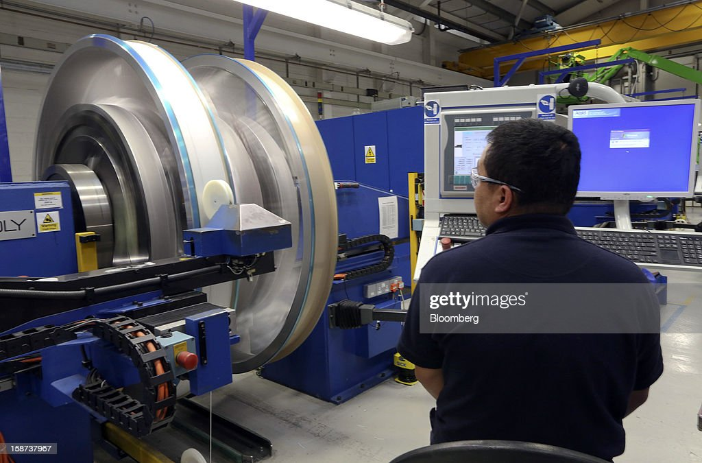 An employee monitors a machine as niobium titanium wire is coiled onto a stainless steel vessel to produce a magnet for use in Magnetic Resonance...