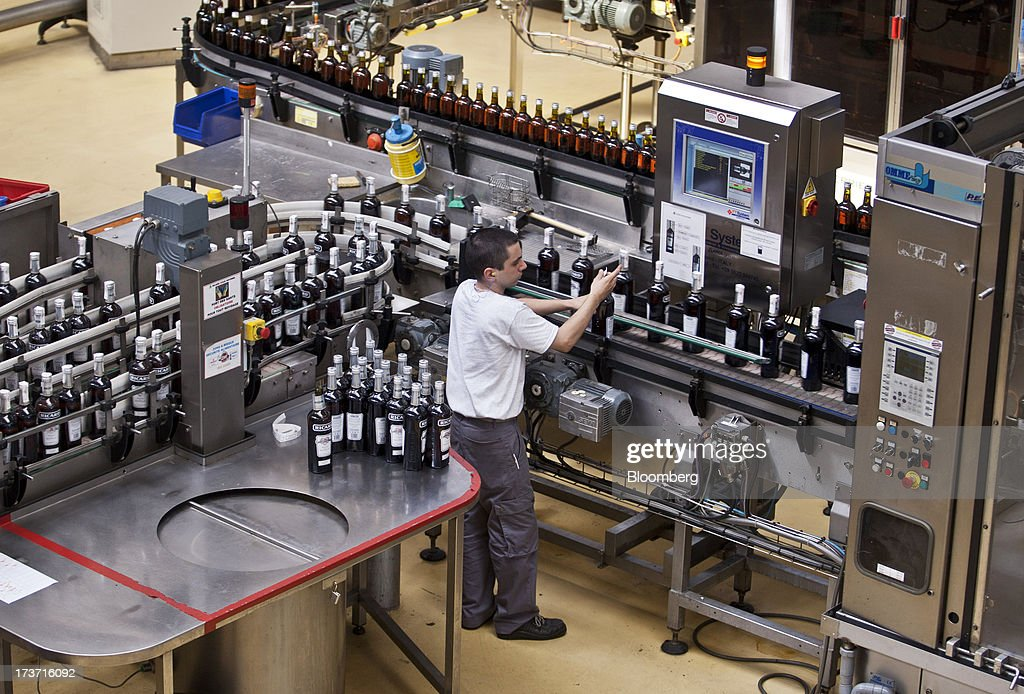 An employee monitors an automated production line conveying bottles of Ricard pastis, produced by Pernod Ricard SA, at the company's plant in Bordeaux, France, on Tuesday, July 16, 2013. Distillers such as Diageo and Pernod Ricard SA are seeking to expand in emerging markets where booming economic growth is creating a burgeoning middle class with more disposable income. Photographer: Balint Porneczi/Bloomberg via Getty Images