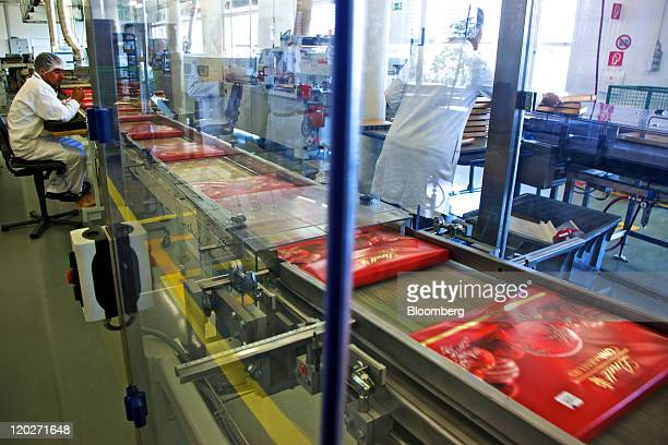 An employee monitors boxes of Lindt chocolate packaged for Christmas on the production line inside the Lindt Spruengli AG factory in Kilchberg near...