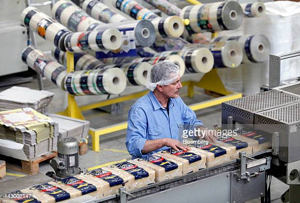 An employee monitors five kilogram packets of parboiled rice as they travel along a conveyor belt ahead of distribution at Riso Scotti SpA's factory...