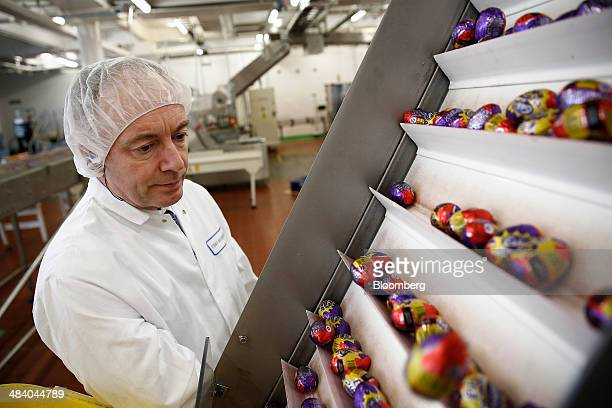 An employee monitors foilwrapped Cadbury Creme Eggs as they move along the production line at the Bournville Cadbury factory operated by Mondelez...