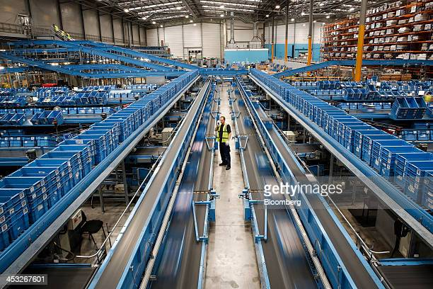 An employee monitors goods as they move in blue crates along an automated production line at an Argos goods distribution center operated by Home...