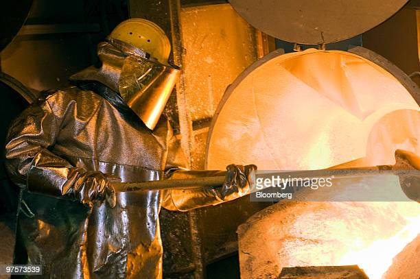 An employee monitors molten copper flowing out of an electric furnance before being cast at the KGHM Miedz owned smelting facility in Glogow Poland...