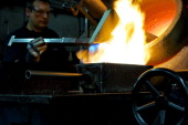 An employee monitors molten silver as it pours from a crucible into a one kilogram mould during the semiautomated gold and silver bar manufacturing...