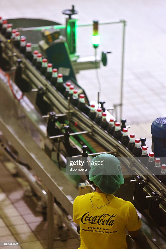 An employee monitors operations as bottles of Coca-Cola soda move along the production line at the Coca-Cola Co. bottling plant in Hmawbi, Myanmar, on Tuesday, June 4, 2013. Coca-Cola Co. Chief Executive Officer Muhtar Kent marked the return of the world's largest soda maker to Myanmar after 60 years by opening a bottling plant and pledging more investment in the newly opened economy. Photographer: Dario Pignatelli/Bloomberg via Getty Images