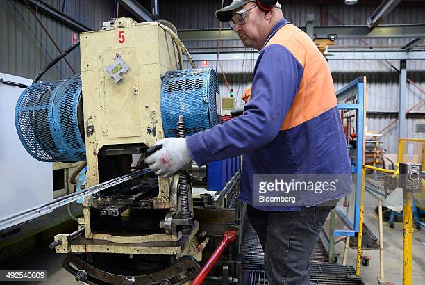 An employee monitors operations as metal tape is threaded through a mill to be formed into shape on the production line at the Backwell IXL plant in...