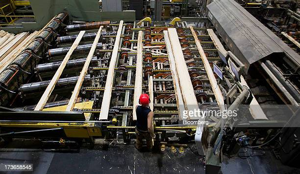 An employee monitors production at the West Fraser Timber Co sawmill in Quesnel British Columbia Canada on Thursday July 11 2013 West Fraser Timber...