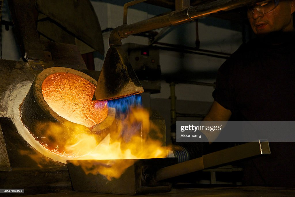 An employee monitors the heating of a freshly cast 400 ounce gold bar during the semiautomated gold bar manufacturing process at a precious metal...
