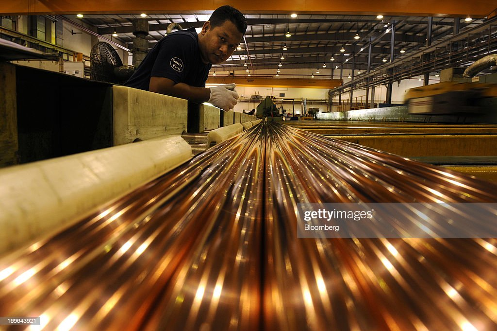 An employee monitors the production of copper rods at the Luvata Malaysia Bhd. plant in Pasir Gudang, Johor, Malaysia, on Monday, May 13, 2013. At a time when copper stockpiles are rising to the highest in a decade, manufacturers are paying the biggest premiums for the metal in as much as seven years as financing deals lock up supply and extend lines at warehouses. Photographer: Munshi Ahmed/Bloomberg via Getty Images