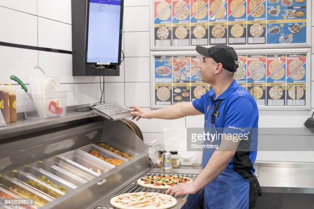 An employee monitors the store delivery system on a screen inside a Domino's Pizza Group Plc store in Hanwell London UK on Monday Feb 27 2017...