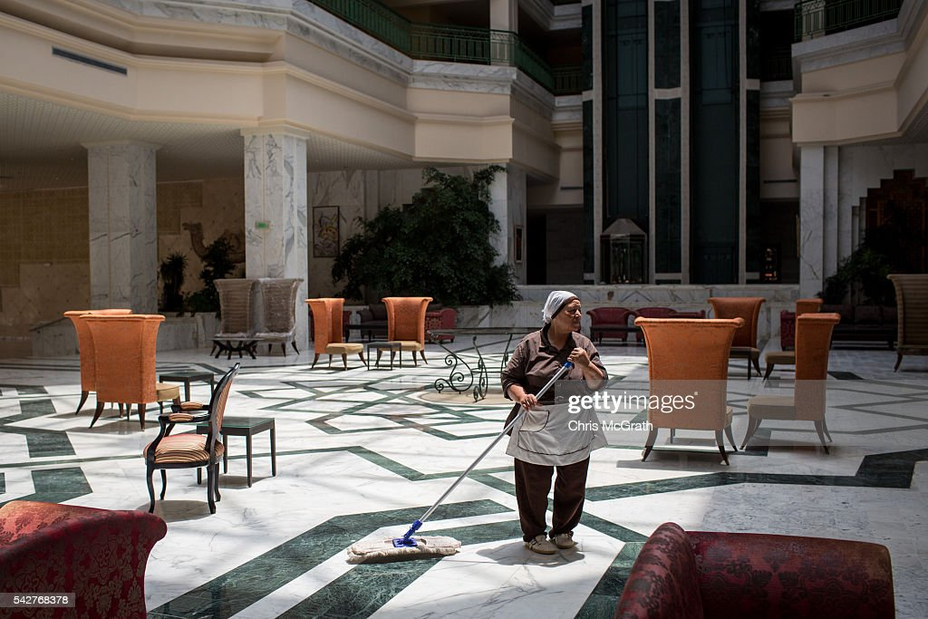 An employee mops the lobby floor at the closed Imperial Marhaba Hotel on June 24, 2016 in Sousse, Tunisia. The Imperial Marhaba hotel was the main target of the 2015 Sousse beach terrorist attack that killed 38 people including 30 Britons. The hotel attempted to stay open for three months after the attacks, however low occupancy forced the hotel to close. Since then it has operated with a skeleton staff, who work to maintain the rooms and grounds, other permanent hotel staff were able to be placed in temporary jobs at two other hotels owned by the same chain. The hotel hopes to open again by next spring or as soon as British travel advisories and restrictions are lifted for Tunisia. Before the 2011 revolution, tourism in Tunisia accounted for approximately 7% of the countries GDP. The two 2015 terrorist attacks at the Bardo Museum and Sousse Beach saw tourism numbers plummet even further forcing hotels to close and many tourism and hospitality workers to lose their jobs. The 26th of June 2016 marks the anniversary of the Sousse beach attacks.