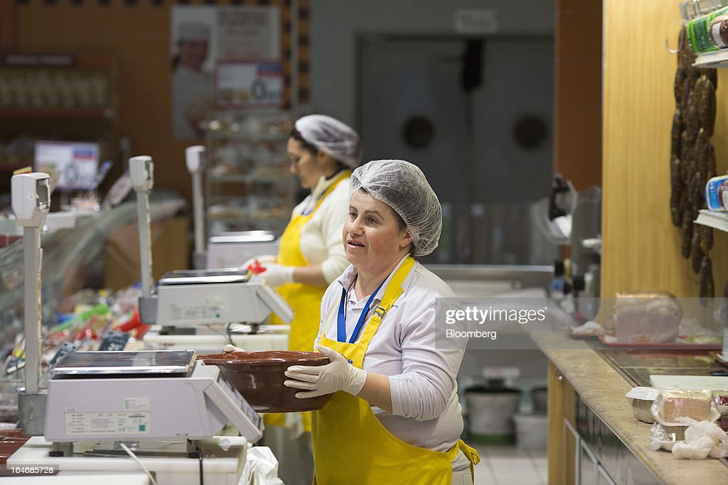 An employee moves a bowl of cheese at the dairy counter of a Carrefour SA supermarket at the Mall of Cyprus in Nicosia, Cyprus, on Tuesday, March 26, 2013. Controls on capital movements to prevent money from draining out of the banking system -- allowed in exceptional circumstances under European Union law -- will remain for 'a matter of weeks,' Cypriot Finance Minister Michael Sarris said. Photographer: Simon Dawson/Bloomberg via Getty Images