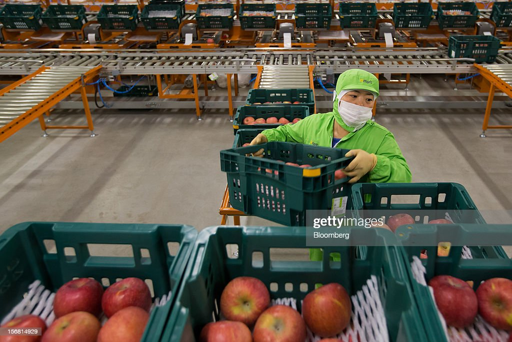 An employee moves a crate of apples at the E-Mart Co. Fresh Center, a sorting facility, in Icheon, South Korea, on Wednesday, Nov. 21, 2012. South Korea's household debt rose to a record in the third quarter as borrowing increased to finance homes and consumption. Photographer: SeongJoon Cho/Bloomberg via Getty Images